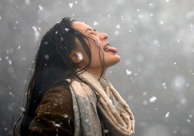 فتاة تحاول التقاط الثلج بلسانها في كاتماندو، نيبال 23 يناير/ كانون الثاني 2019