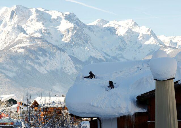 جنود يشاركون في إزالة الثلوج الكثيفة من على سطح منزل في ويرفنوينغ، النمسا 16 يناير/ كانون الثاني 2019