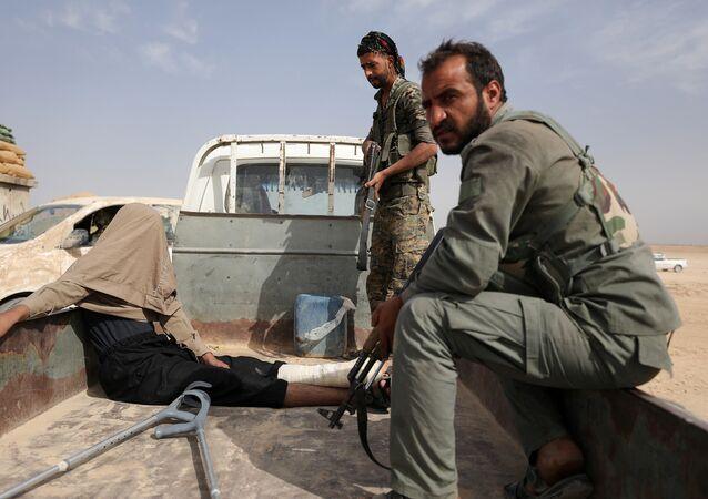 مقاتلون من قوات سوريا الديمقراطية بعد القبض على جريح أثناء قتالهم مع داعش في المنطقة الشمالية من دير الزور في سوريا