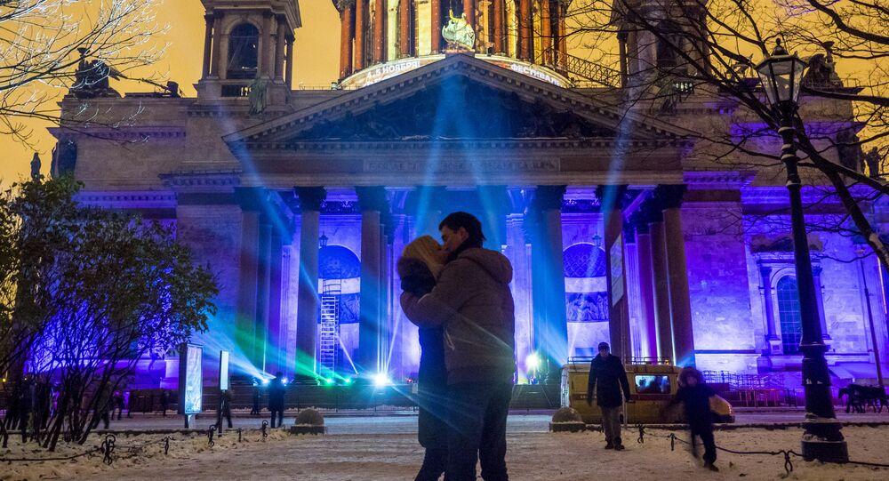 شخصان على خلفية عرض ضوئي مهرجان دائرة الضوء-2016 في سان بطرسبورغ