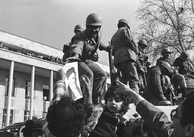 فتاة إيرانية صغيرة تقف على دبابة مأسورة عند مدخل قصر نيافاران حيث كان شاه محمد رضا بهلوي يعيش في طهران