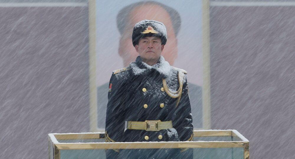 أحد أفراد الحرس العسكري يقف أمام صورة الرئيس الصيني الراحل ماو تسي تونغ أثناء تساقط الثلوج في ميدان تيانانمين في بكين بالصين في 12 فبراير/ شباط 2019