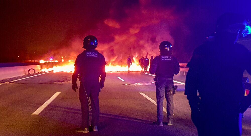 رجال الشرطة يقفون إلى جوار الحواجز المشتعلة بالقرب من جيرونا