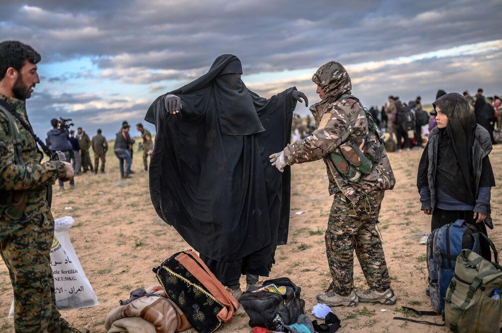 عضو في القوات الديموقراطية السورية قسد يتفحص امرأة بعد أن غادرت آخر موقع كان تحت سيطرة تنظيم داعش الإرهابي (المحظور في روسيا) في باغوز، في محافظة دير الزور شمال سوريا، 27 فبراير/ شباط 2019.