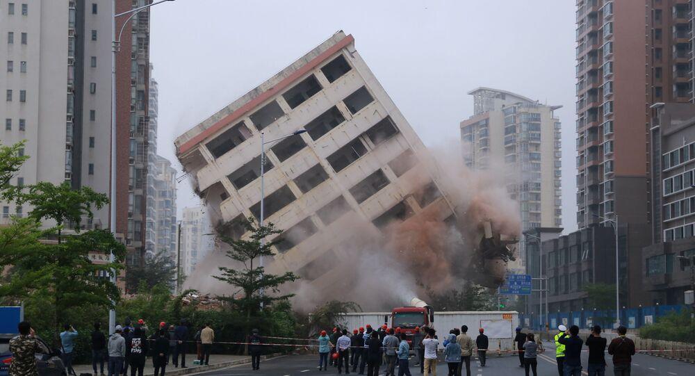 مواطنون يراقبون عملية هدم مبنى مكون من ثمانية طوابق يقع على طريق في هايكو بمقاطعة هاينان، الصين في 24 فبراير/ شباط 2019