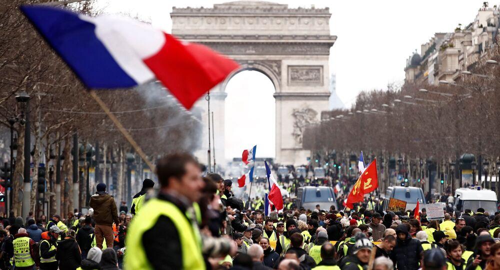 أحد المتظاهرين يرتدي سترة صفراء يلوح بعلم فرنسي وهو يقف على الشانزليزيه بالقرب من قوس النصر أثناء مظاهرة حركة السترات الصفراء في باريس