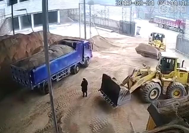 سائق جرافة لم يلاحظ الفتاة وجرفها مع كومة الرمل وألقاها في الشاحنة