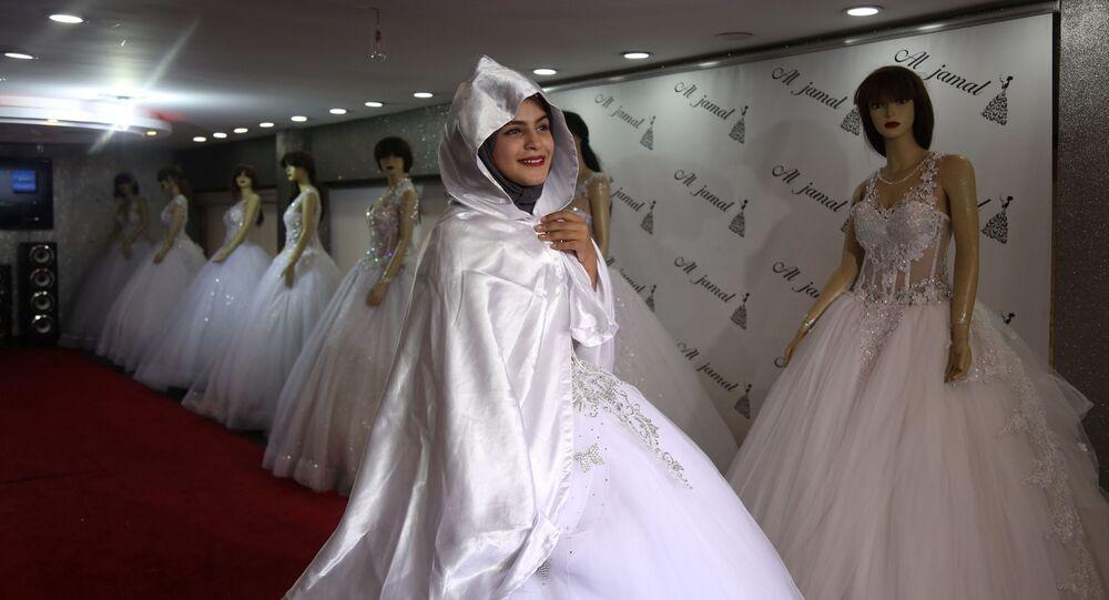الشابة الفلسطينية هناء أبو الروس، 18عاما، طالبة الثانوية العامة، تجرب فستان زفاف في إطار التجهيز لحفل زفافها في متجر في مدينة غزة، 26 نوفمبر/ تشرين الثاني 2018