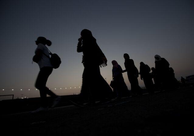 فلسطينيون يسيرون باتجاه معبر قلنديا في مدينة رام الله الفلسطينية