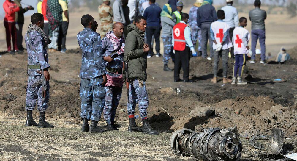 رجال من الشرطة الفيدرالية الإثيوبية يقفون بالقرب من أجزاء المحرك في مكان تحطم طائرة الخطوط الجوية الإثيوبية بالقرب من مدينة بيشوفو