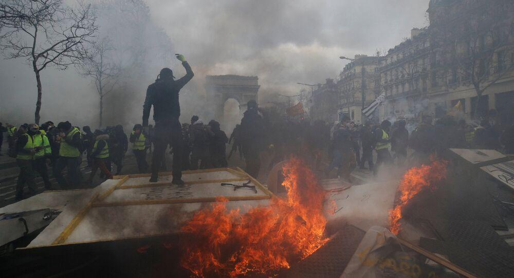 متظاهر يقف على حاجز محترق أثناء مظاهرة من قبل حركة السترات الصفراء في باريس