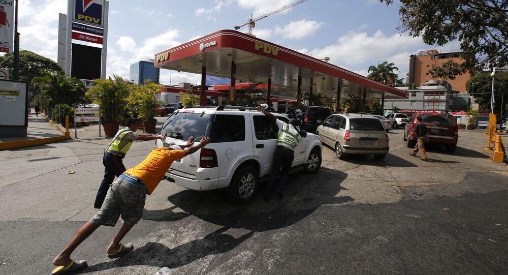 أشخاص يدفعون بالسيارة إلى محطة بنزين، بها مولد كهربائي خاص بها، أثناء انقطاع التيار الكهربائي في كراكاس، 10 مارس/ آذار 2019