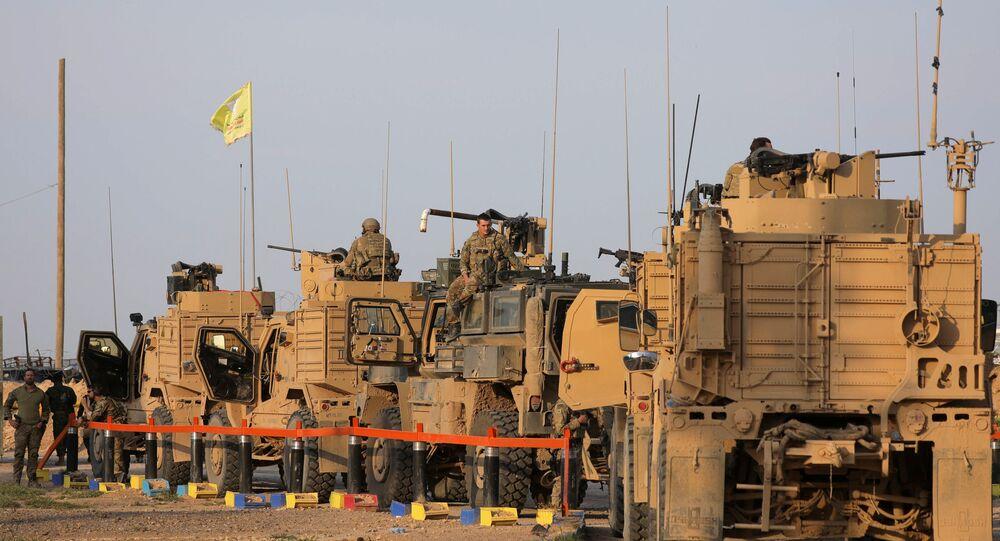 جنود أمريكيون يقفون بالقرب من شاحنات عسكرية في حقل العمر في دير الزور