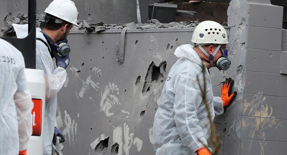 خبراء الشرطة الإسرائيلية في الموقع الذي أصيب فيه منزل بصاروخ شمالي تل أبيب بإسرائيل