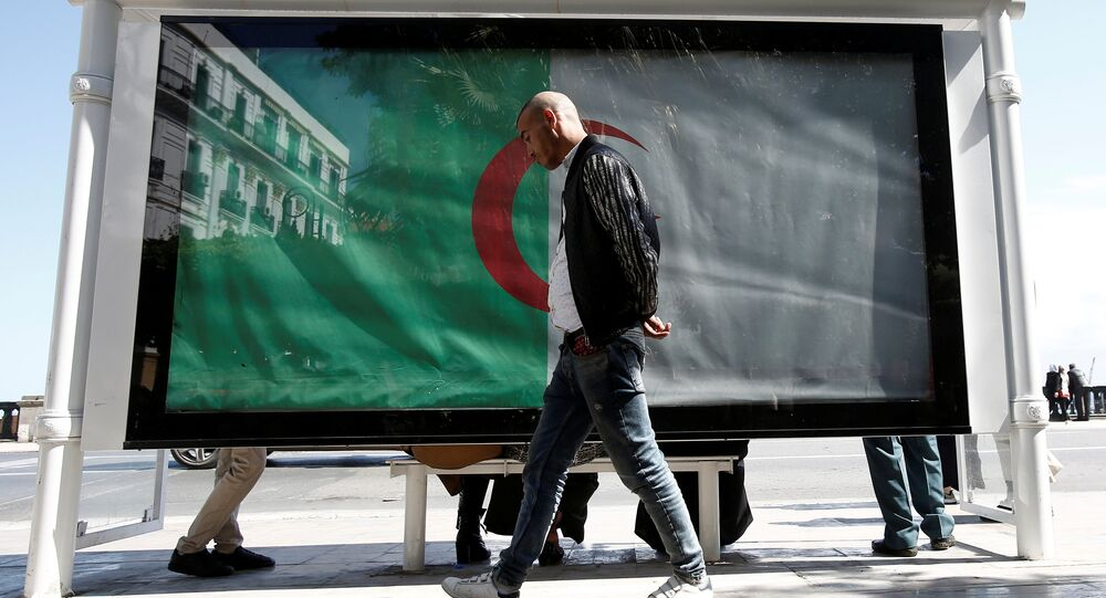 رجل يسير بجوار العلم الوطني الجزائر العاصمة