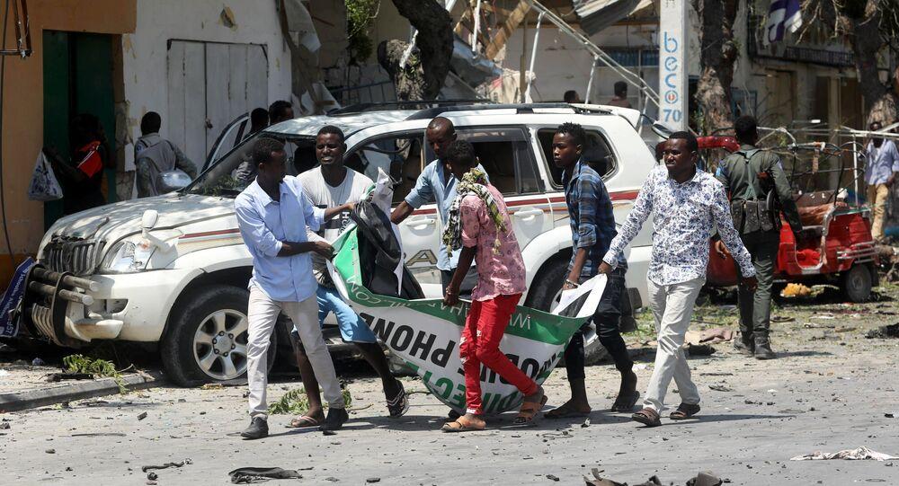 مدنيون يحملون جثة رجل قتل في انفجار سيارة مفخخة بالقرب من فندق في مقديشو