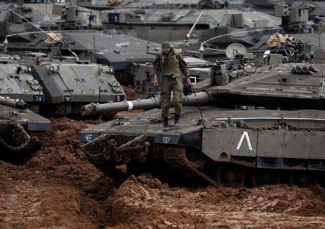 جندي إسرائيلي يقف على دبابة بالقرب من الحدود مع قطاع غزة، 27 مارس/ آذار 2019