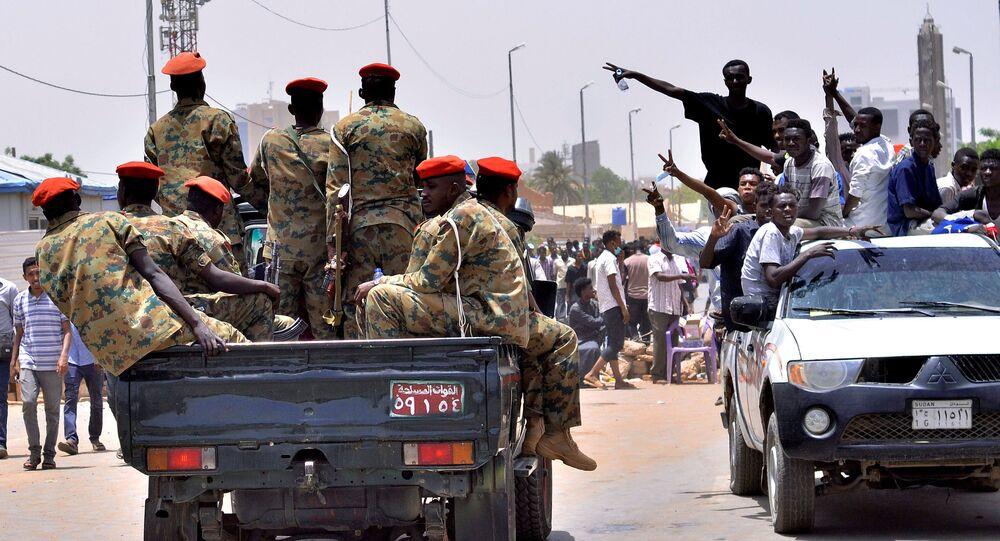 مظاهرات سودانية تحتفل وهي تسير باتجاه مركبة عسكرية بالقرب من وزارة الدفاع في الخرطوم