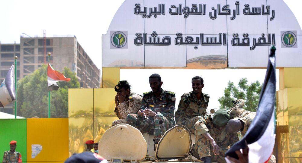 أفراد من الجيش السوداني يجلسون على حاملة جنود مدرعة بالقرب من وزارة الدفاع في الخرطوم