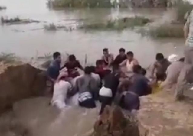 شباب يصنعون بأجسادهم حاجز لصد المياه في إيران