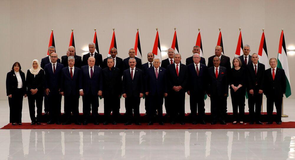 الرئيس الفلسطيني محمود عباس مع أعضاء الحكومة الفلسطينية الجدد أثناء أداءهم اليمين الدستورية