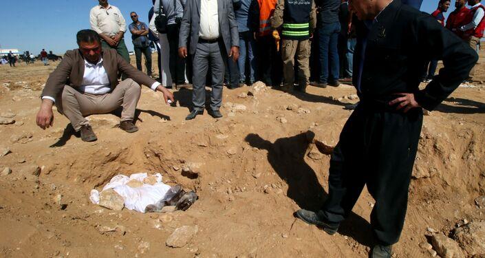 رجال أكراد ينظرون إلى العظام المغطاة من مقبرة جماعية اكتشفت للأكراد في غرب مدينة السماوة