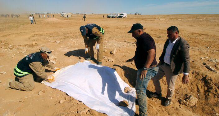 أعضاء من الدفاع المدني العراقي يغطون عظام مقبرة جماعية مكتشفة للأكراد غرب مدينة السماوة