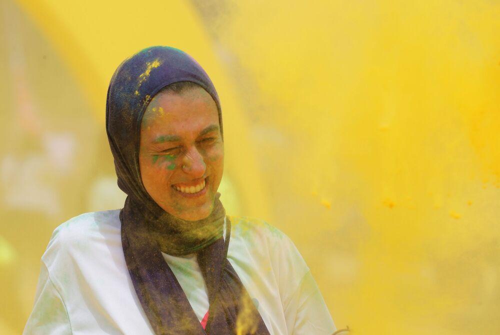 متطوعون يصبون مسحوقا من اللون الأصفر على المتسابقين الذين اجتازوا خط نهاية السباق، في أول مسابقة الألوان في الجيزة، مصر في 13 أبريل/ نيسان 2019
