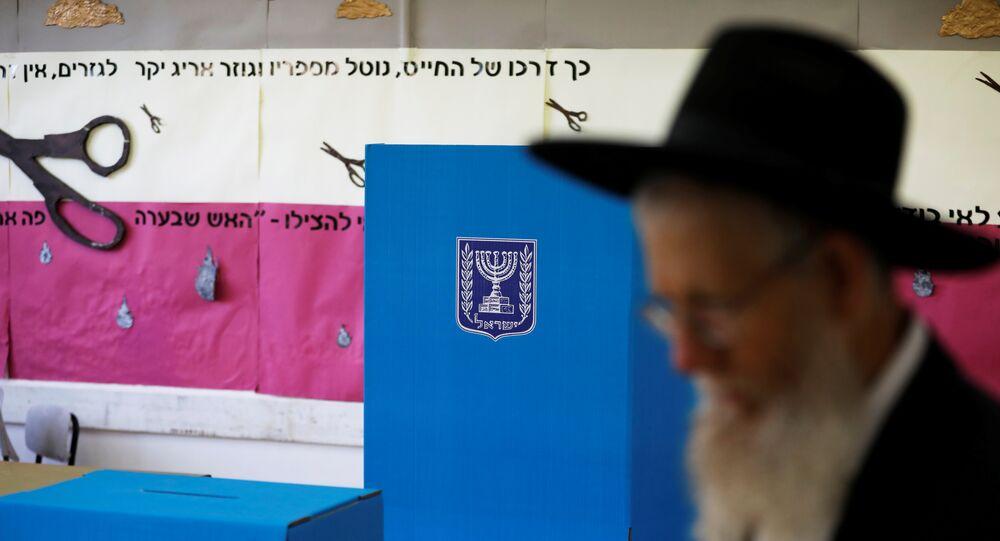 رجل يهودي متشدد يمشي بجانب كشك الاقتراع وصندوق الاقتراع في مركز اقتراع بينما يصوت الإسرائيليون في الانتخابات البرلمانية في القدس