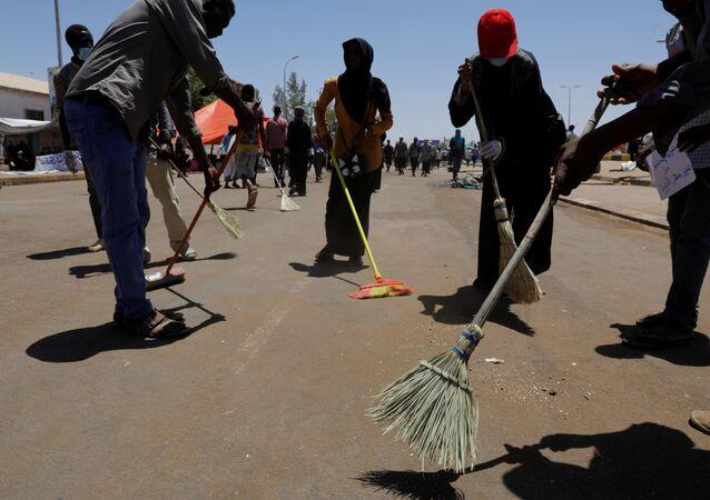 متظاهرون سودانيون يكنسون الطريق أثناء احتجاج أمام وزارة الدفاع في الخرطوم