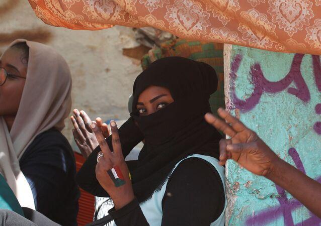 متظاهرات يرفعن علامات النصر أمام وزارة الدفاع في الخرطوم