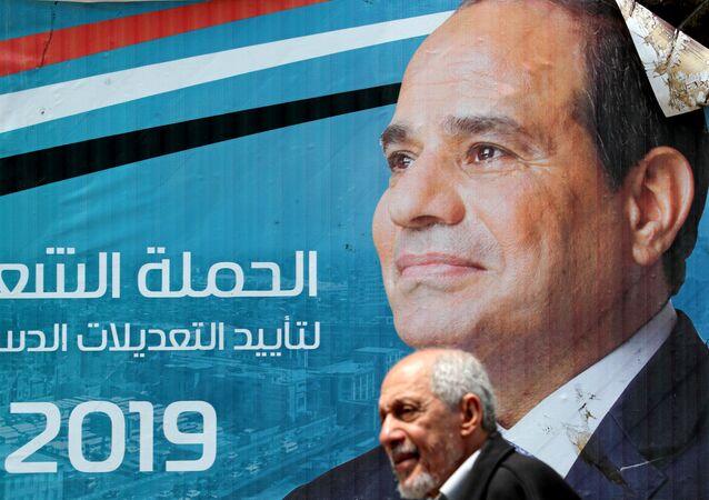 رجل يمشي أمام لافتة تصور الرئيس المصري عبد الفتاح السيسي قبل الاستفتاء على التعديلات الدستورية في القاهرة