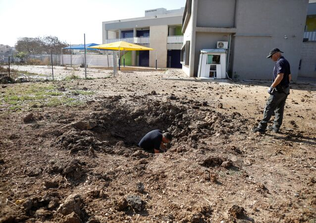 ضباط شرطة إسرائيليين يتفقدون موقع سقط فيه صاروخ أطلق من غزة