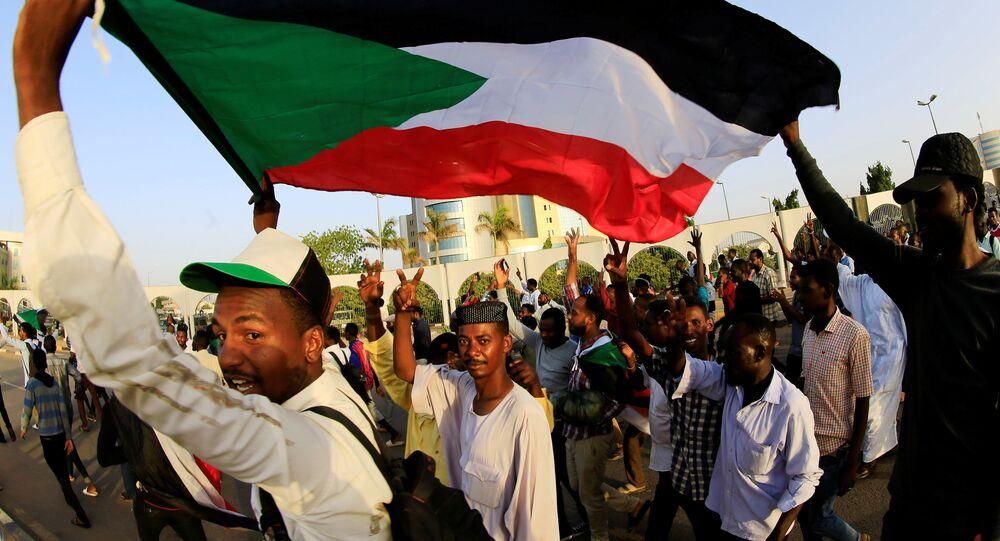 متظاهرون سودانيون يحملون العلم الوطني وهم يهتفون قبل الإفطار في اليوم الأول من شهر رمضان أمام مجمع وزارة الدفاع في الخرطوم