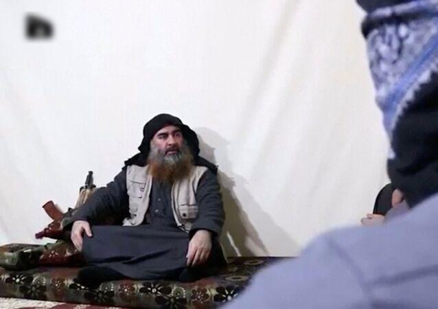 رجل ملتح مع زعيم داعش أبو بكر البغدادي في صورة التي التقطت من شريط فيديو نُشر في 29 أبريل 2019
