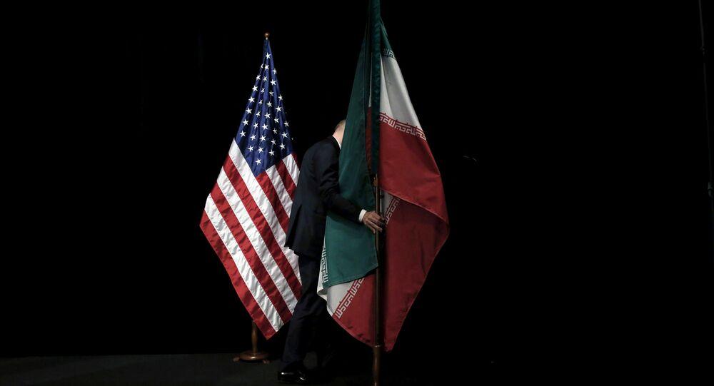 موظف يرفع العلم الإيراني من المسرح بعد صورة جماعية مع وزراء الخارجية وممثليهم خلال المحادثات النووية الإيرانية في مركز فيينا الدولي في فيينا
