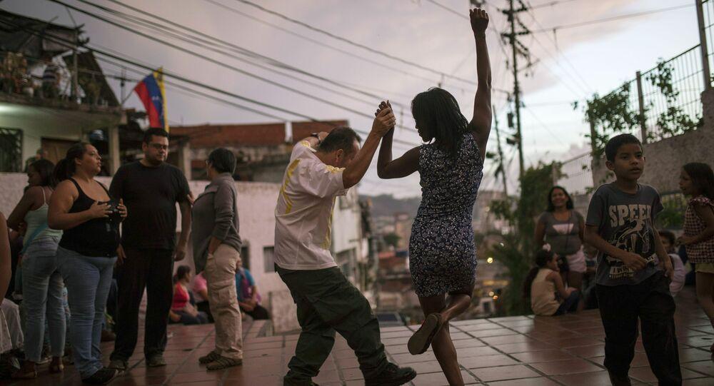 شخصان يرقصان على عزف موسيقيين في ساحة عامة حيث يجتمع الجيران في كاراكاس، فنزويلا، عند غروب الشمس السبت 11 مايو/ أيار 2019