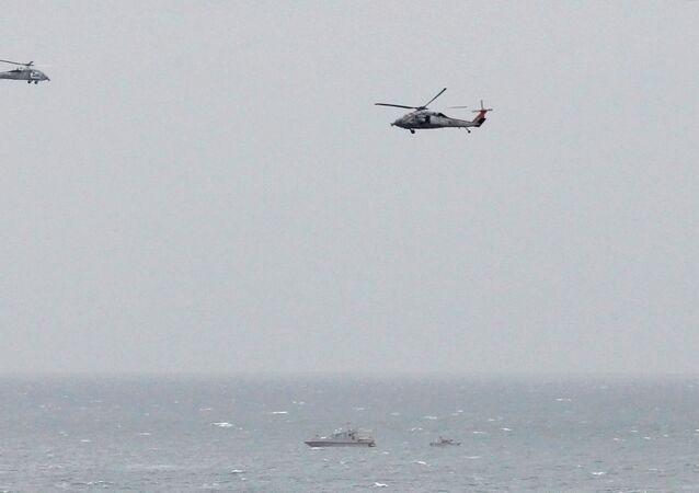 زورق للحرس الثوري الإيراني بالقرب من حاملة الطائرات الأمريكية جورج دبليو بوش في مضيق هرمز بينما تحلق مروحيات تابعة للبحرية الأمريكية في مكان قريب
