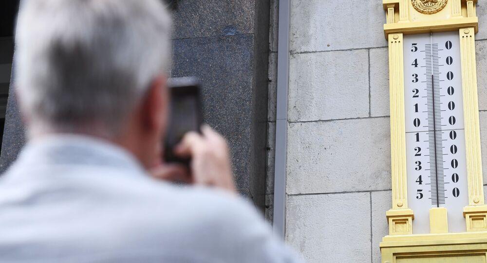 رجل يلتقط صورة لجهاز قياس الحرارة المثبت على مبنى مجلس الدوما الروسي في موسكو