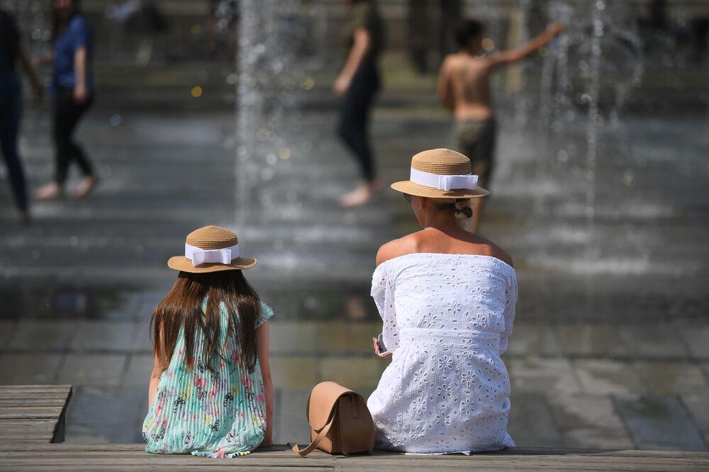 الأم وانبتها تجلسان بجوار نافورة حديقة موزيون في موسكو