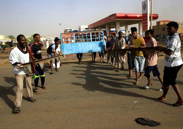 متظاهرون سودانيون يقيمون حاجزًا في أحد الشوارع لمطالبة المجلس العسكري الانتقالي في البلاد بتسليم السلطة إلى المدنيين