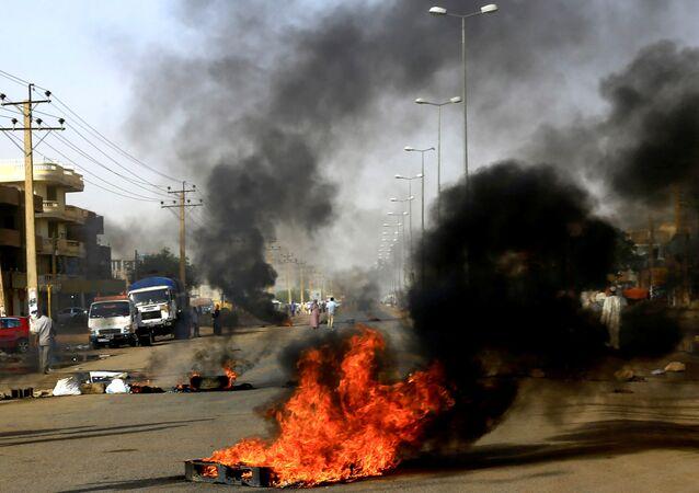 متظاهرون سودانيون يستخدمون الإطارات المحترقة لإقامة حاجز في أحد الشوارع