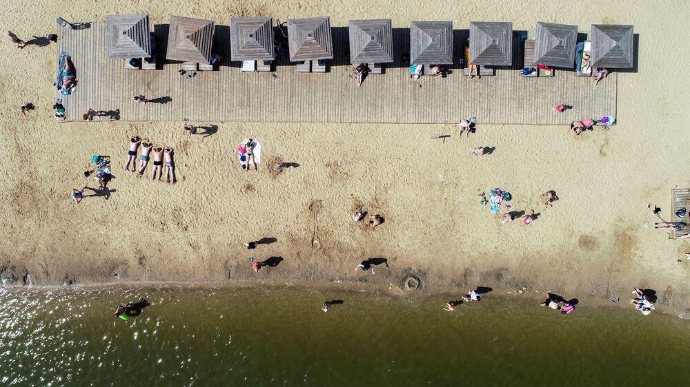 المصطافون على شاطئ منطقة ميشيرسكويه للترفيه والاستجمام في موسكو