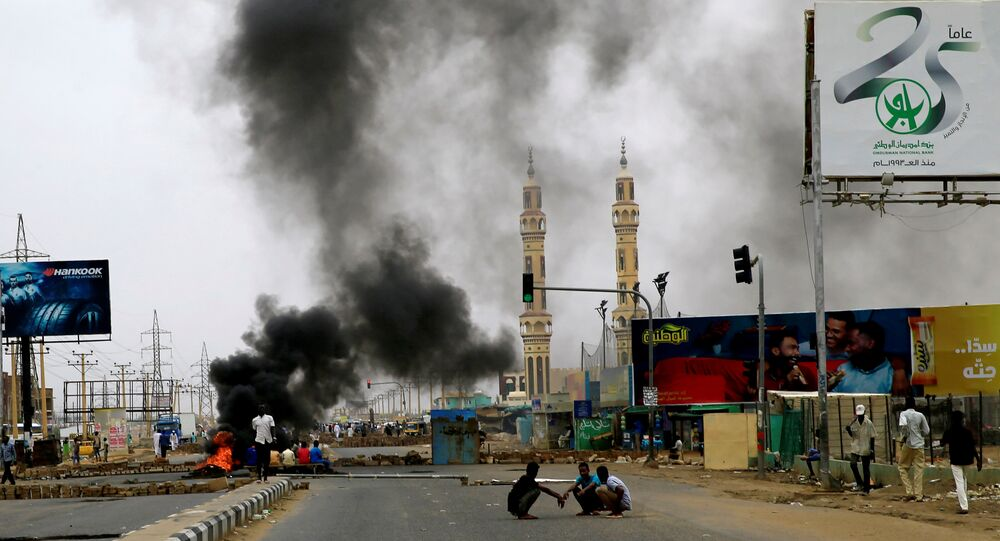 متظاهرون سودانيون بالقرب من إطارات محترقة مستخدمة لإقامة حاجز في أحد الشوارع مطالبين المجلس العسكري الانتقالي في البلاد بتسليم السلطة للمدنيين