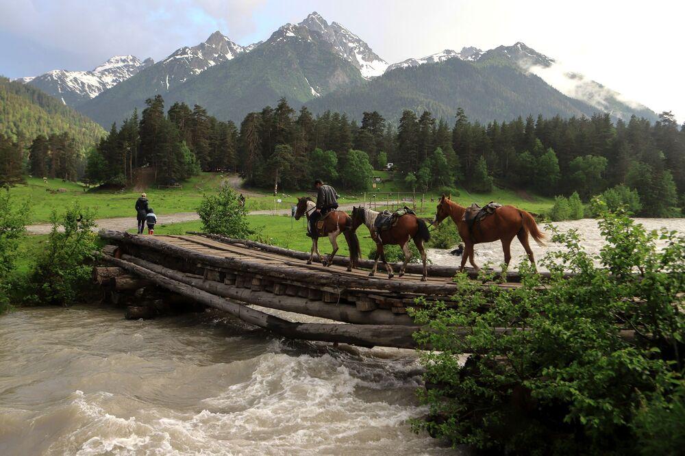 أحد راكبي الخيول يعبر جسرا خشبيا فوق نهر جبلي في أراضي وادي صوفيا في جمهورية كراتشاي - تشركيسيا