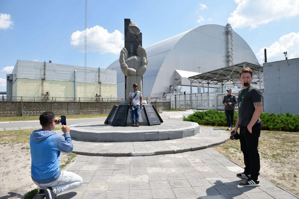 سياح يلتقطون صورة تذكارية على خلفية نصب تذكاري الذي شيد لمكافحي كارثة تشيرنوبل