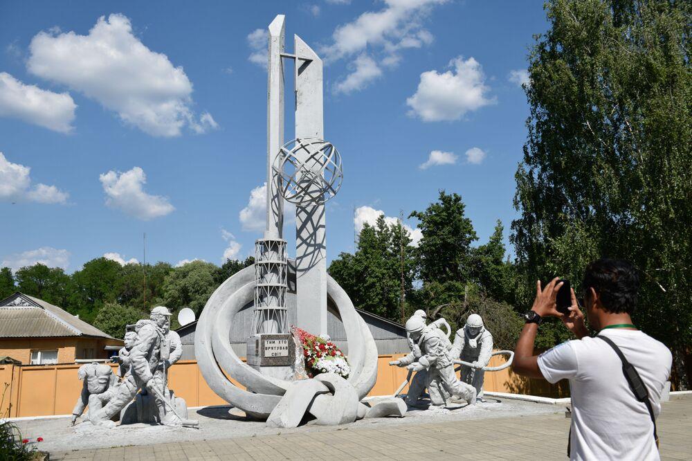 سياح يلتقطون صورة تذكارية على خلفية نصب تذكاري الذي شيد لمكافحي كارثة تشيرنوبل (التمثال يحمل اسم لولئك الذين أنقذوا العالم.