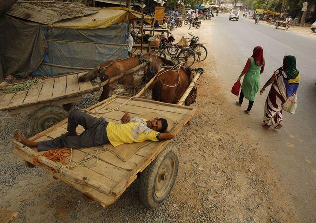 رجل نائم على عربة أثناء موجات الحر في ضواحي براياغراي، الهند، 13 يونيو/ حزيران 2019