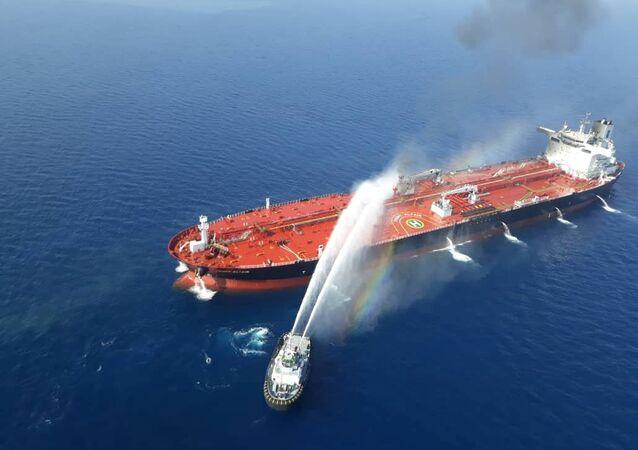 قارب بحرية إيرانية يحاول إيقاف النيران المشتعلة في ناقلة النفط بعد أن تعرضت للهجوم في خليج عمان، 13 يونيو/حزيران 2019