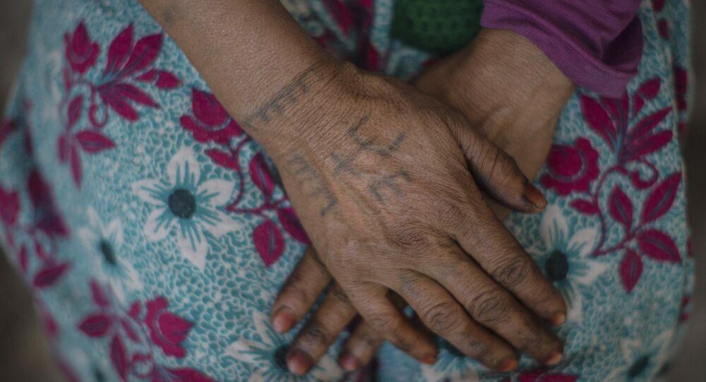 سيدة من الأمازيغ ترسم وشما لعلم الأمازيغية